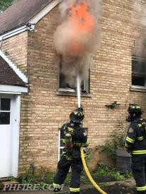 A firefighter makes an initial attack on one fire.