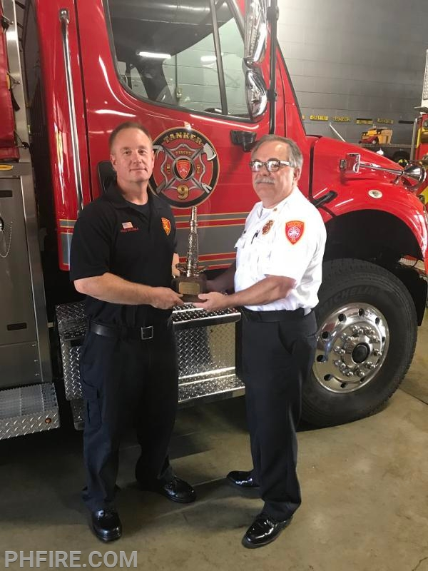 Fire Chief Drew Smith presenting a 30 year award to FF/PM Doug Golonka