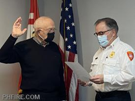 Fire Chief Smith administering to Mr. John Goode the fire commissioner Oath of Office.