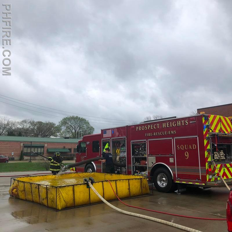 Firefighters deploy hard suction hose into portable water tank to practice drafting (sucking the water). Drafting is used when fire hydrants are insufficient or not present.